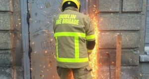 A member of  Dublin Fire Brigade cuts a door to gain access to  Belcamp College on Friday to deal with a fire.  Photograph: Dublin Fire Brigade