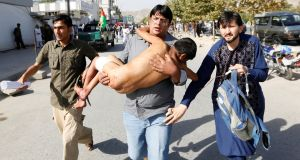 A man carries an injured boy outside a hospital after a suicide bombing in Kabul, Afghanistan. Photograph: Mohammad Ismail/Reuters
