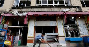 An Afghan man removes broken glass from his shop on Sunday, a day after a suicide attack in Kabul, Afghanistan. Photograph: Reuters