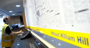 A man fills out a betting slip in a William Hill betting shop in the borough of Mayfair in London.