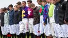 Jockeys stand for a minutes silence in memory of JT McNamara. Photograph: INPHO/Ryan Byrne