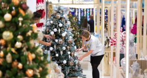 An employee arranges a display on a Christmas tree during the opening day of the Christmas shop in the Selfridges, London,  Monday. Photograph: Jason Alden/Bloomberg