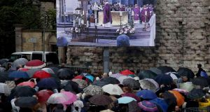 Mourners gather in the rain near a screen outside the Cathedral in Rouen, France, where the funeral service in memory of Fr Jacques Hamel is taking place. Photograph: Jacky Naegelen/Reuters.