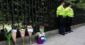 Floral tributes rest against railings near the scene of a stabbing in Russell Square, London, in which a woman was killed and five people injured.  Photograph: Jonathan Brady/PA Wire