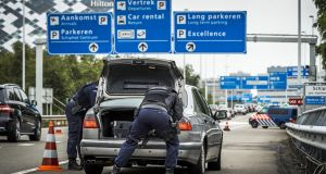 Dutch police officers search a car boot on the high way to Schiphol Airport in Amsterdam. Photograph: Remko de Waal/AFP/Getty Images