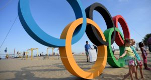 Children pose next to the Olympic rings on Copacabana beach in Rio. Photograph: AFP / Kirill Kudryavtsev / Getty Images