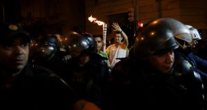 A man carries the Olympic torch surrounded by police along the streets of Copacabana. Photograph: AP / Gregory Bull