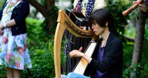 Junshi Morakami played the Irish Harp during the annual commemoration for the victims of the Hiroshima atomic bomb at the memorial cherry tree at Merrion Sq. Photograph: Cyril Byrne/The Irish Times