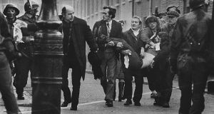 Edward Daly runs down the street with an injured man on 'Bloody Sunday' on January 30th 1972