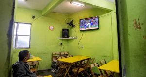 A man watches the Olympics in a bar in the Rio favela of Rocinha. Photo: James Crombie/Inpho