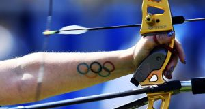 A tattoo of the Olympic rings is seen on the forearm of Switzerland's Christine Bjerendal as she shoots an arrow during the Rio 2016 Olympic Games women's competition at the Sambodromo archery venue in Rio de Janeiro, Brazil. Photograph: Jewel Samas/AFP/Getty Images