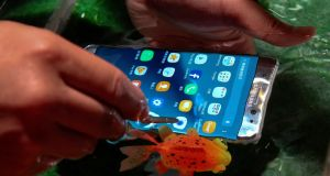 A visitor tries a Galaxy Note 7, the newest phablet from Samsung Electronics, submerged under water in Taipei