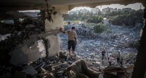 A Palestinian man stands in the remains of his living room shortly after his home was hit by an Israeli airstrike in Gaza City in August 2014. Photograph: Oliver Weiken/EPA