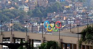 A favela community crowds on a hill behind the Olympic Rings at Maracana Stadium, Rio. Photograph: EPA