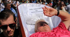 A 'corpse' shields her eyes from the sun at the Near Death festival in Las Nieves
