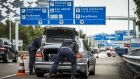 Dutch police officers search a car boot on the way to Schipol Airport in Amsterdam. Photograph: Remko De Waal/AFP/Getty Images