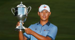 Si Woo Kim of South Korea poses with the trophy after winning the final round of the Wyndham Championship at Sedgefield Country Club. Photograph: Kevin C. Cox/Getty Images
