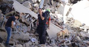 ITALY QUAKE: Rescuers and firemen inspect the rubble of buildings in Amatrice, central Italy, after a powerful earthquake rocked the area. At time of publication the quake had left at least 73 people dead. Photograph: Filippo Monteforte/AFP/Getty Images