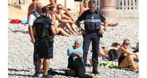 A woman in a headscarf was photographed on a beach in Nice removing a long-sleeved top while surrounded by armed police. Photograph: Poppy Gold