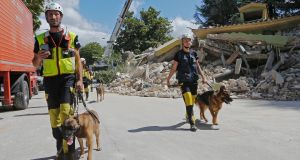 Rescue workers with sniffer  dogs following an earthquake in Amatrice, Italy. The dogs have a tough time dealing with dust in their noses. Photograph: Ciro De Luca/Reuters