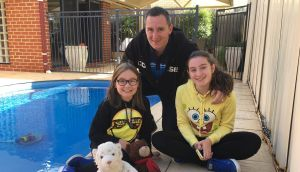 Mark Cunningham poolside with his daughters Olivia and Kerri in Perth.