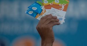 A man holds up Olympics tickets to sell in Rio de Janeiro, Brazil. The OCI's executive committee played no role in appointing the council's authorised ticket reseller for the Rio Games, a review has found. File photograph: Chris McGrath/Getty Images