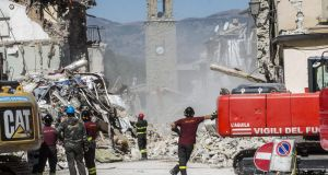 Members of the Italian fire brigades operate near civic tower, in the earthquake-stricken town of Amatrice, on Monday. Photograph: Massimo Percossi/EPA