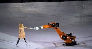 A performer interacts with a robotic arm during the opening ceremony. Photograph Sergio Moraes/Reuters  .