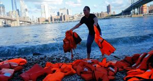 An Oxfam worker holds lifejackets  collected from the beaches of Chios, Greece and used by adults and children. They are on display at the Brooklyn Bridge park ahead of the UN Summit for Refugees and Migrants in New York on Monday. Photograph: Kena Betancur/AFP/Getty Images