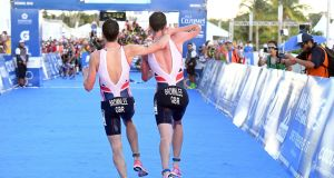 Alistair Brownlee helps his brother Jonny to get to the finish line during the Triathlon World Series event in Cozumel Mexico. Photograph: AP