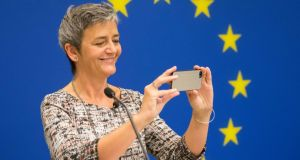 European commissioner for competition Margrethe Vestager uses an Apple iPhone to take a picture of the room from the podium as her news conference begins in Washington on Monday. Photograph: Michael Reynolds/EPA