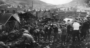 Helpers filling sandbags on the tip above the shattered Pantglas Junior School to divert a spring and avert the risk of further landslides at Aberfan, South Wales. Photograph: Fox Photos/Getty Images