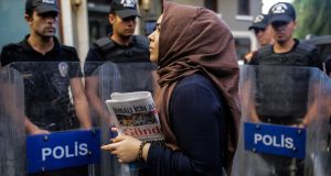 A woman holding the Ozgur Gundem newspaper, one of the outlets ordered to close by a Turkish court. Photograph: Yasin Akgul/AFP/Getty Images