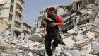 A Syrian man carries a baby after removing him from the rubble of a destroyed building following a reported air strike in the Qatarji neighbourhood of  Aleppo on Wednesday. Photograph:  Ameer Alhalbi/AFP/Getty Images