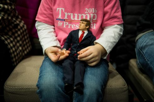 Charlee Dotson, 3, plays with a Donald Trump action figure as she waits with her father, Matt Dotson, before the start of a campaign event with Trump,  at the DoubleTree by Hilton Hotel Cedar Rapids Convention Complex in Cedar Rapids, Iowa, Feb. 1st. Photograph: Damon Winter/The New York Times