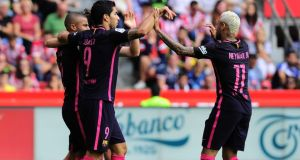 Barcelona teammates Luis Suarez and Neymar celebrate a goal at El Molinon stadium in Gijon. Photograph: Getty Images