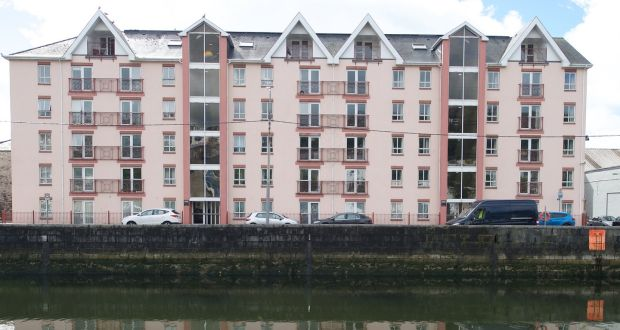 the block of apartments are along the banks of the river lee in cork city