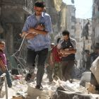 Syrian men carrying babies make their way through the rubble of destroyed buildings following a reported air strike on the rebel-held Salihin neighbourhood of the northern city of Aleppo. Photograph: Ameer Alhalbi/AFP/Getty Images