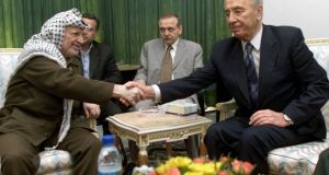 Former Israeli foreign minister Shimon Peres, right, and the late  Yasser Arafat shake hands at a meeting in 2001.  Photograph: AP Photo/Ahmed Jadallah