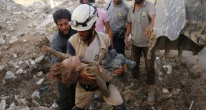 "A Syrian civil defence volunteer, known as the ""white helmets"", holds the body of a child after he was pulled from the rubble following a government forces air strike on the rebel-held neighbourhood of Karm Homad in the northern city of Aleppo, on October 4th, 2016. Photograph: AFP/Getty Images"