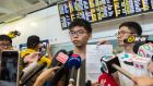 Hong Kong democracy campaigner Joshua Wong (centre) stands next to recently-elected lawmaker Nathan Law  as he holds up his expulsion order from Thai authorities  upon his arrival  in Hong Kong on Wednesday. Photograph: Anthony Wallace/AFP/Getty Images