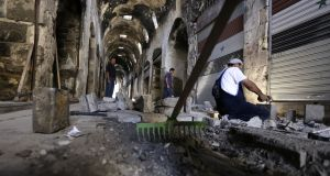 Members of the United Nations Development Programme perform restoration work in a damaged alley of the ancient market in the heart of the mostly government-controlled Syrian city of Homs. Photograph: Louai Beshara/AFP/Getty Images