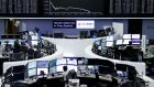 Traders work at their desks in front of the German share price index, DAX board, at the stock exchange in Frankfurt, Germany. Deutsche Bank rebounded 3.4 per cent.