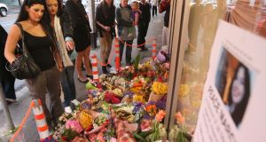 People look at floral tributes outside the front of the Duchess Boutique on Sydney Rd, the store which captured the last CCTV footage of Jill Meagher on September 28th, 2012 in Melbourne, Australia. Photograph: Scott Barbour/Getty Images