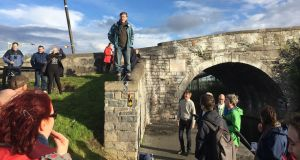 Prof Anthony O'Farrell addressing the walkers at Broome Bridge, with the plaque marking William Rowan Hamilton's discovery of quaternions behind.