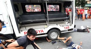 Protesters lie on the ground after being hit by a police van during a rally in front of the US embassy in Manila on October 19th, 2016.  Photograph: AFP/Getty Images