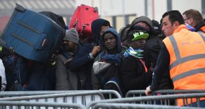 Migrants arrive at an official meeting point in the camp. Photograph: Denis Charletdenis/Getty Images