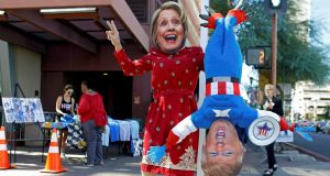 A man wears a mask depicting Democratic US presidential candidate Hillary Clinton while holding a doll depicting Republican  nominee Donald Trump in Phoenix, Arizona, on October 2th. Photograph: Ricardo Arduengo/Reuters