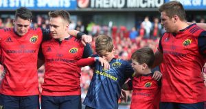 Anthony Foley's sons Tony and Dan with Munster players at Thomond Park, Limerick, last Saturday. Tony's Facebook campaign is hashtagged #8masses4no8. Photograph: Lorraine O'Sullivan/PA Wire
