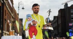 Sergiu Ciobanu celebrates winning the Irish national marathon championship with his on Daniel, aged 4 months, at the SSE Airtricity Dublin Marathon at Merrion Square in Dublin. Photograph:   Stephen McCarthy/Sportsfile